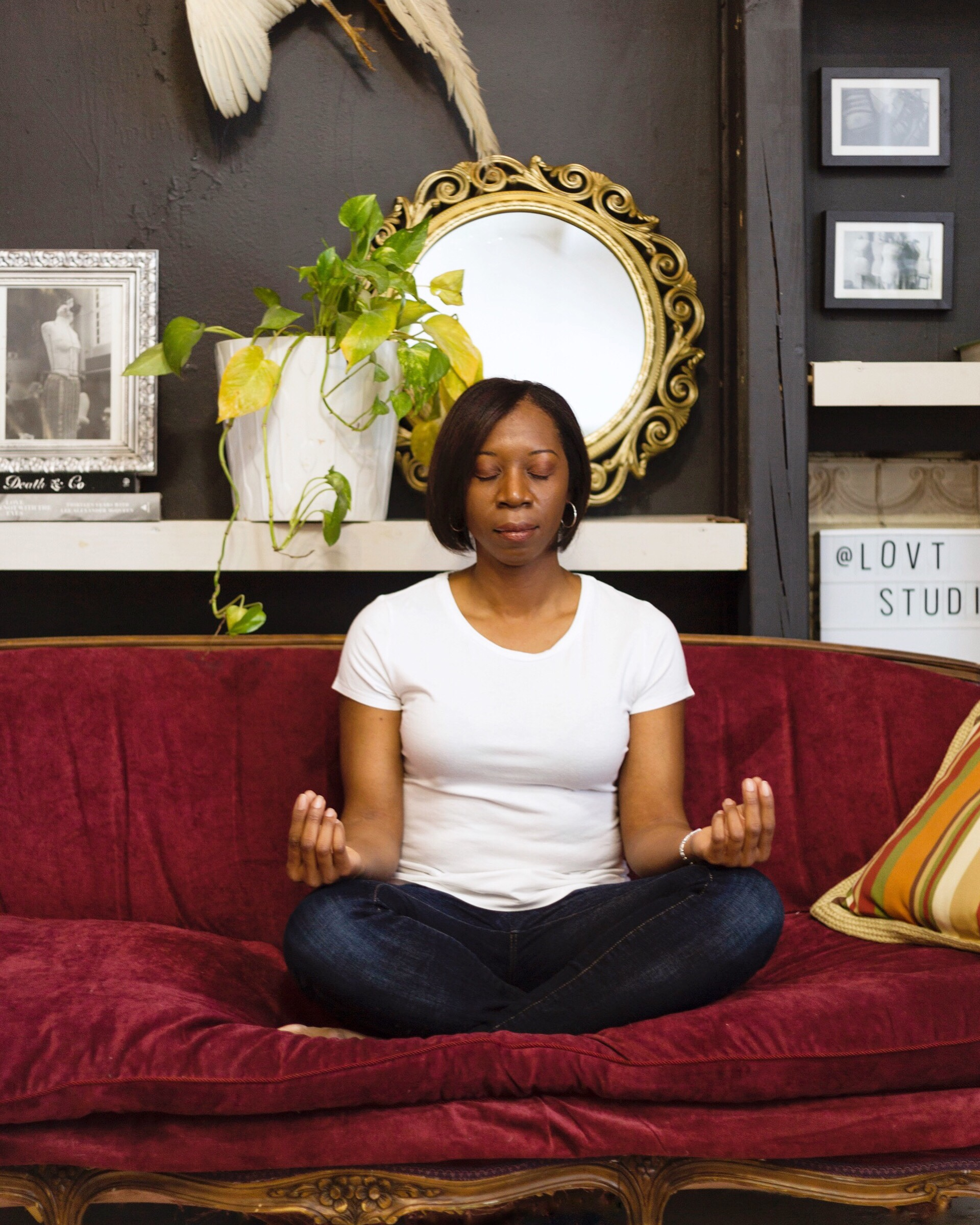 Woman sitting cross-legged on sofa with eyes closed in meditation