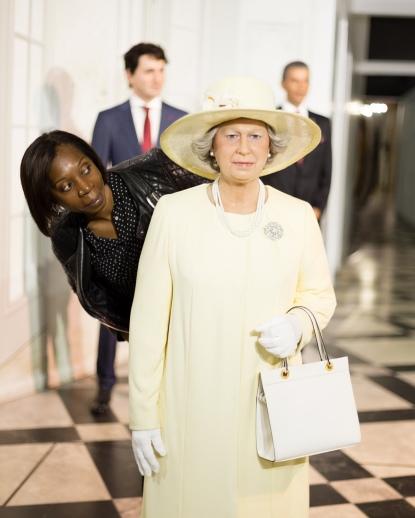 Woman standing beside wax statue of Queen Elizabeth in wax museum