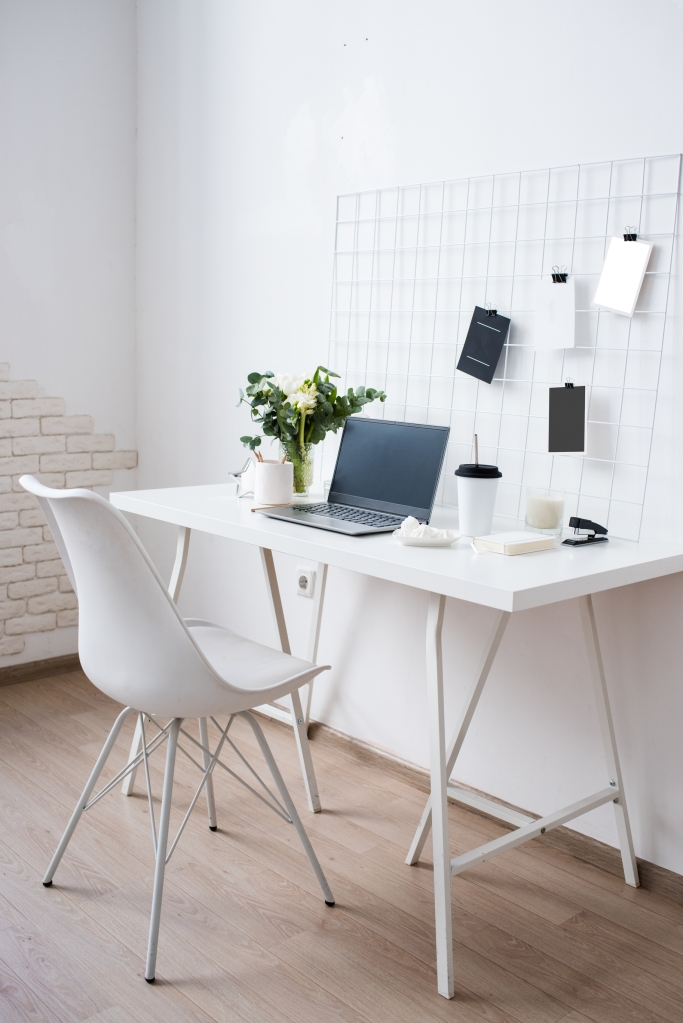 white minimalist workspace, white chair and simple white desk with laptop, plant, coffee cup and papers