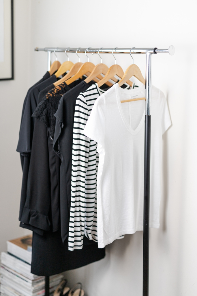 Metal rolling rack of black and white minimalist clothing hanging neatly on wooden hangers