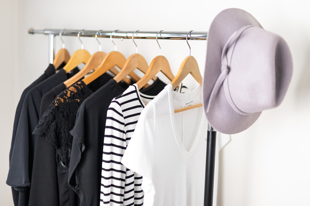 Rolling rack of stylish, minimalist wardrobe pieces and a trendy pale purple broad-rimmed felt had