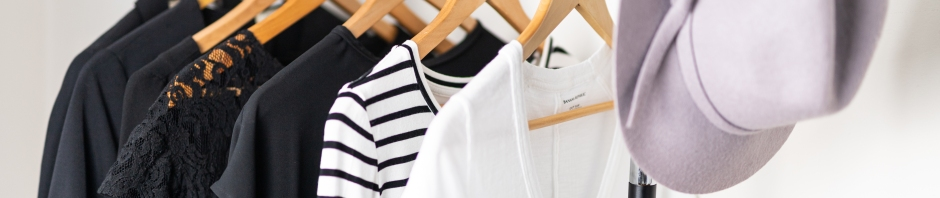 Minimalist style clothing hung on wooden hangers a clothing rack