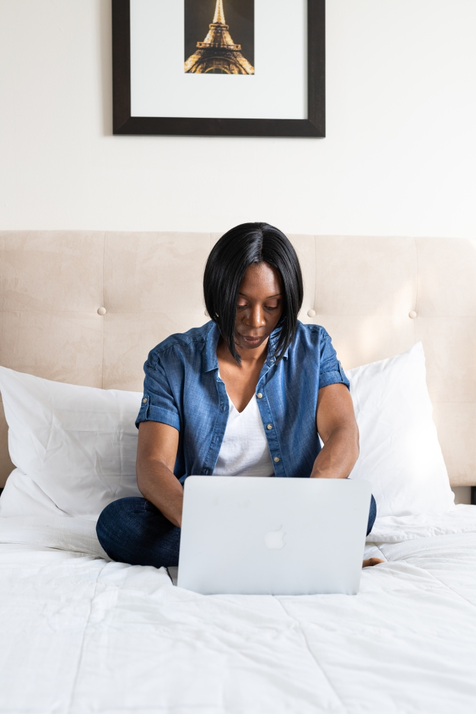 Woman sitting on a bed working on a laptop