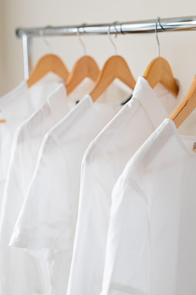 A small selection of white clothing hanging on wooden hangers