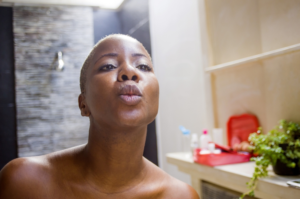 African American woman blowing a kiss to a bathroom mirror