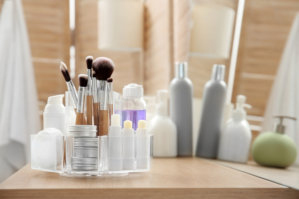 Makeup brushes and beauty products in clear organizer container on a bathroom counter