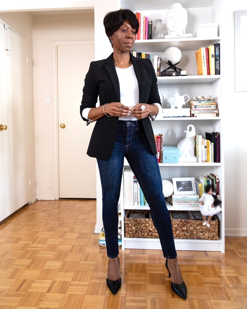black woman wearing dark wash blue skinny jeans, black heels, a black blazer and white t-shirt