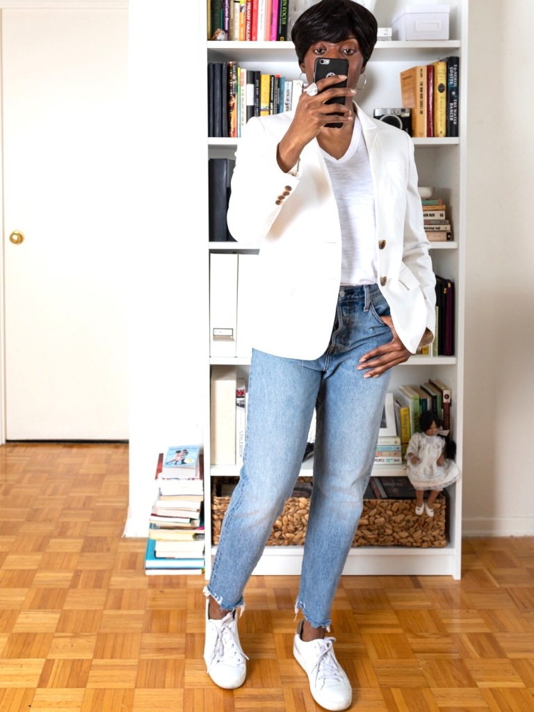 Black woman wearing white blazer an cropped denim