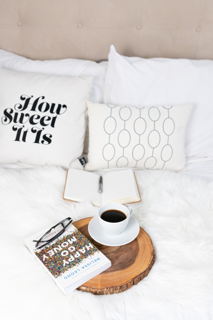 Photo of a Happy Go Money personal finance book on a breakfast tray with a cup of coffee on a bed.