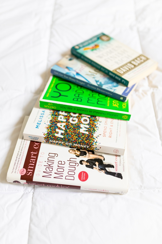 a small collection of personal finance books fanned out on a bed