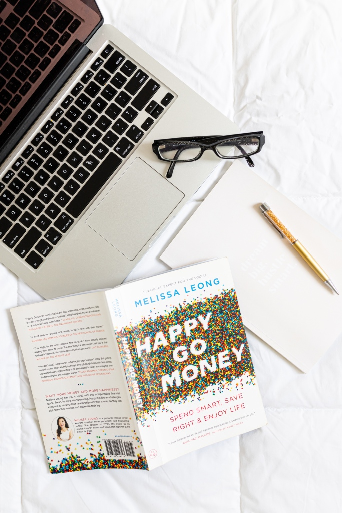 overhead shot of a personal finance book - Happy Go Money, and a laptop, notebook and glasses